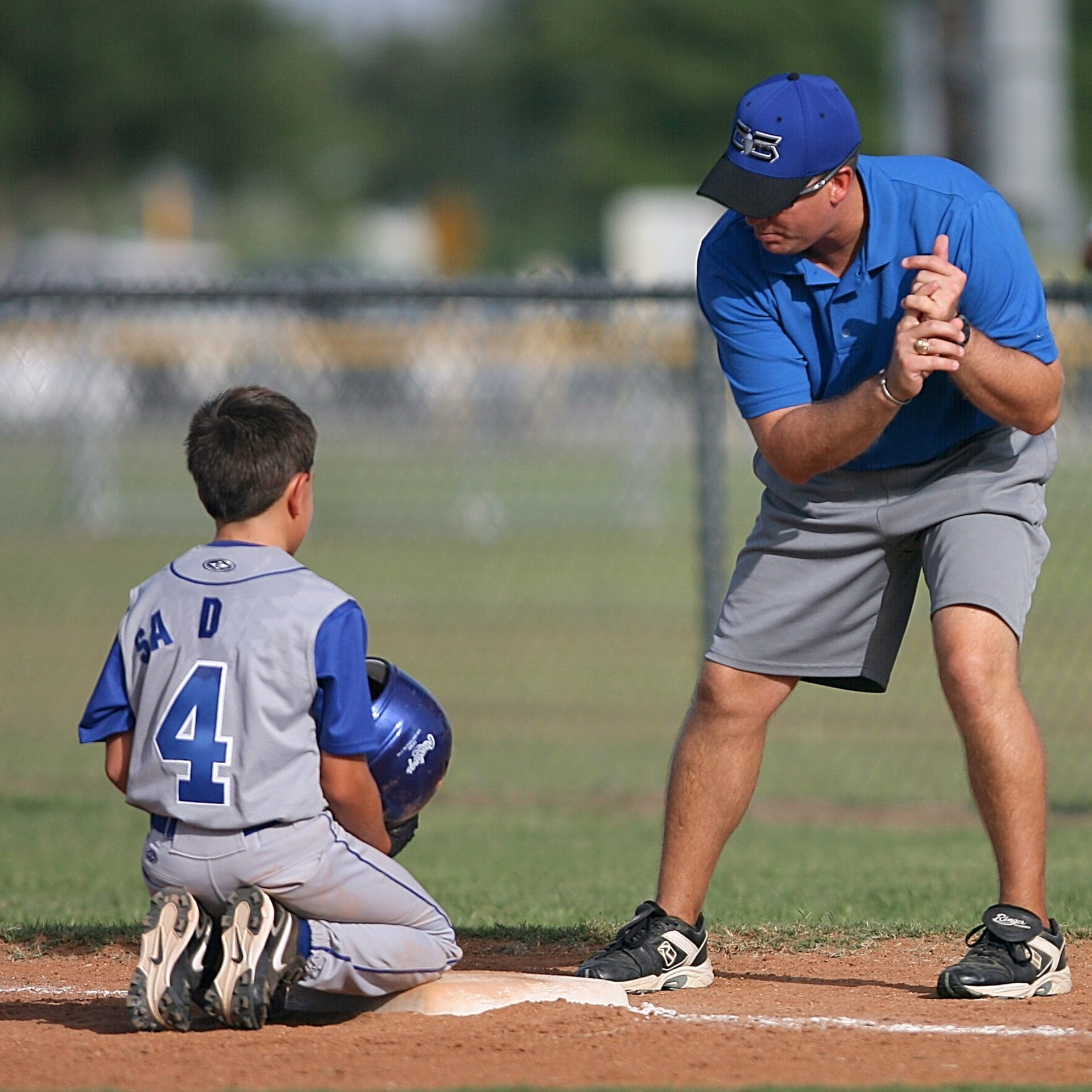 boy Kneeling on Baseball Field Beside Man